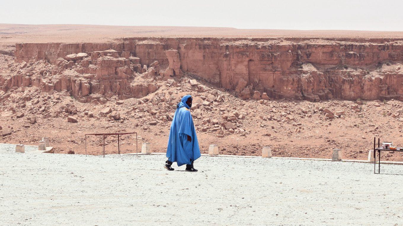 Szahara és kék ruhás személy